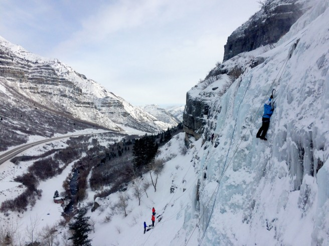 An ice climber nears the top of a climb while others stand below