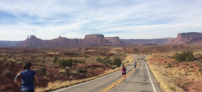 Landscape photo of a race with runners in foreground and desert mesas in background