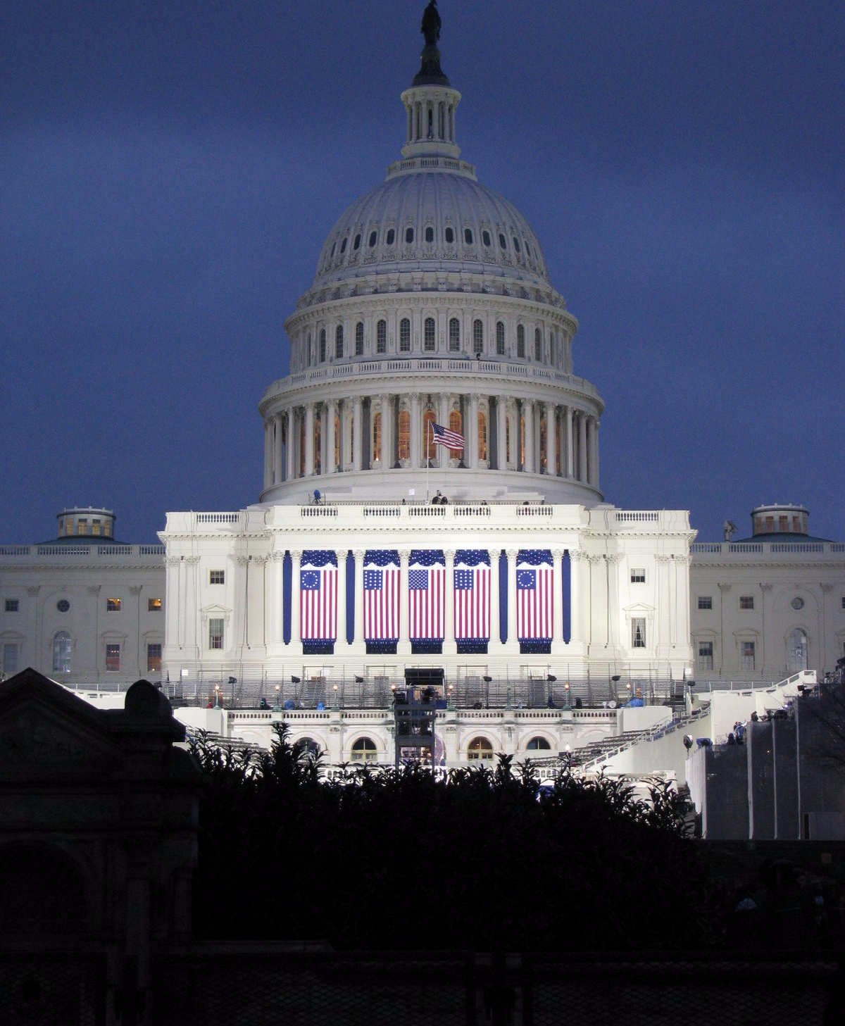 The United States capitol building in the dark, adorned in American flags and spotlights