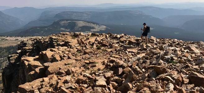 Person trekking across a rocky mountain top with more mountains in the background