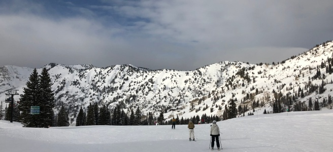 View from top of a ski run with skiers in foreground and Wasatch mountains in background