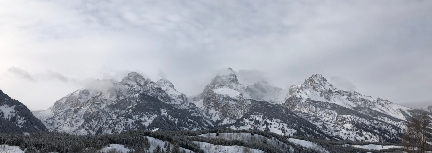 Snow-covered Teton mountains rise behind a wooden fence