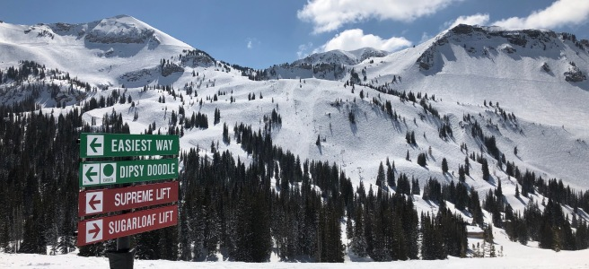Landscape photo of a snow-covered mountain with directional ski trail signs in the foreground