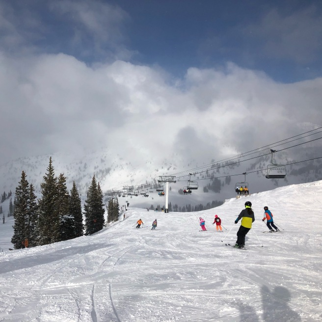 Skiers ski down a mountain and under a chairlift